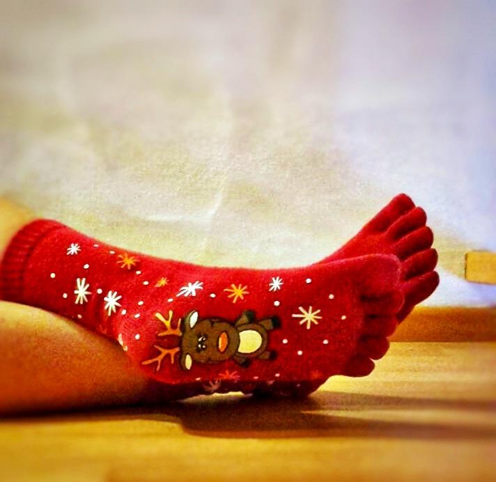 Rote Zehenstoppersocken mit einem Elch an den Fußsohlen, inmitten von Schneeflocken.