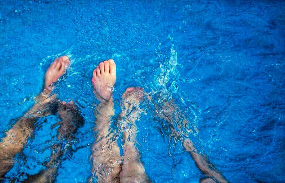 Planschende Beinpaare in leuchtend blauem Wasser.