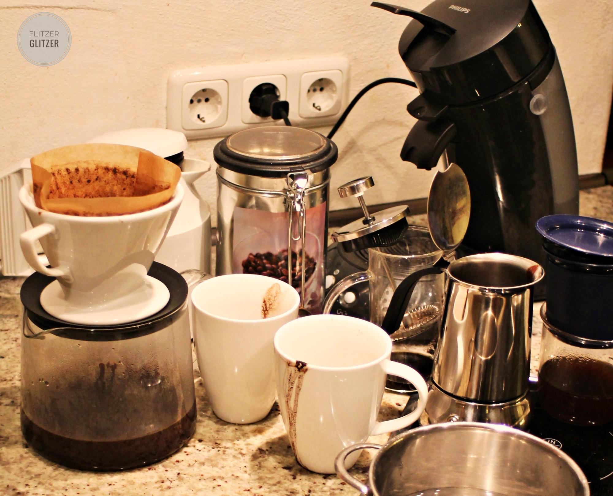 """Das Bild zeigt die Ansammlung einiger Kaffeezubereitungsgeräte aus Glitzers Versuchsreihe. Alles in Allem ziemlich """"benutzt"""", d.h. eingesaut."""