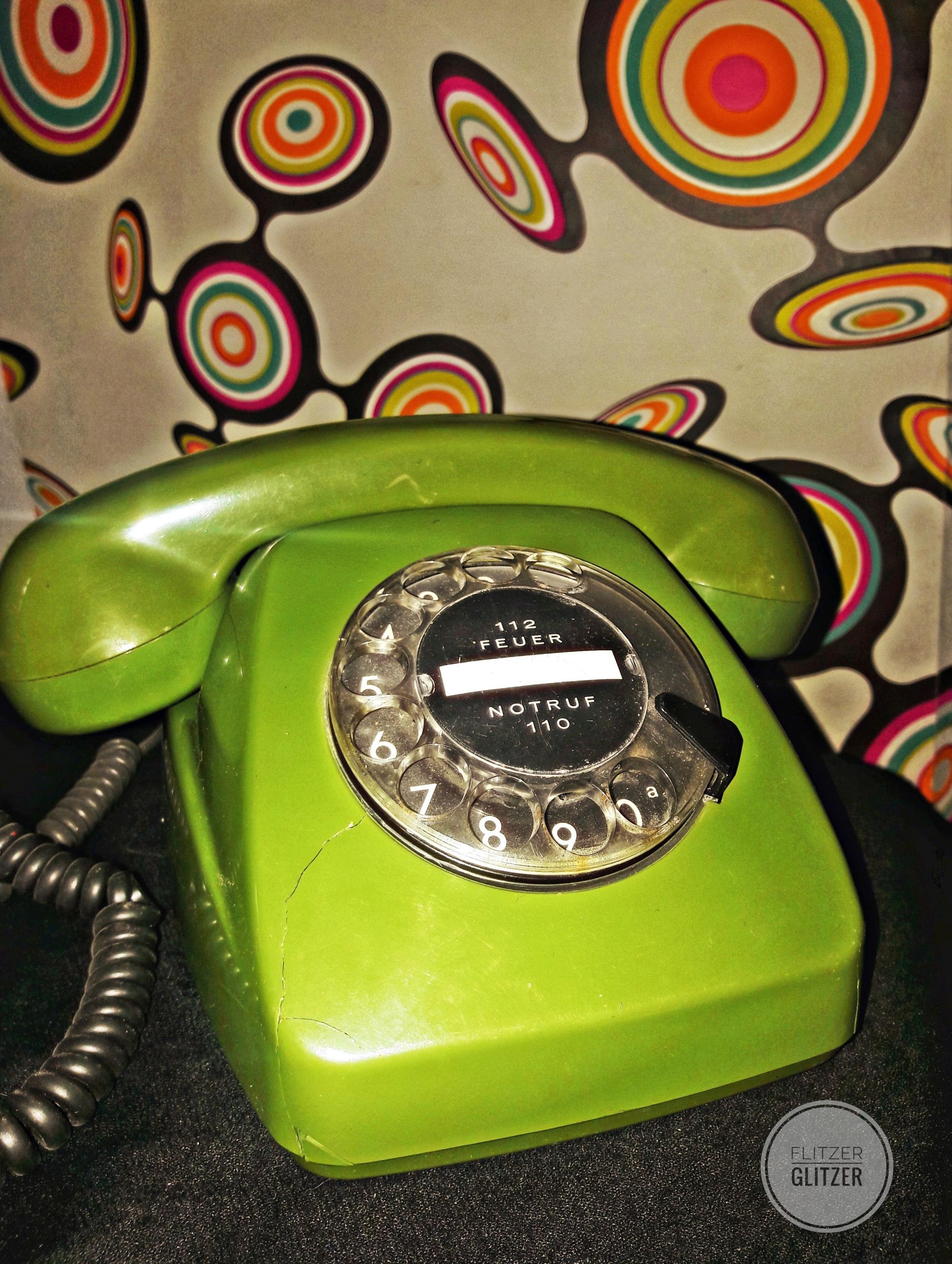 Ein grünes Wählscheibentelefon, vor dem Hintergrund einer farbenfrohen Retrotapete.