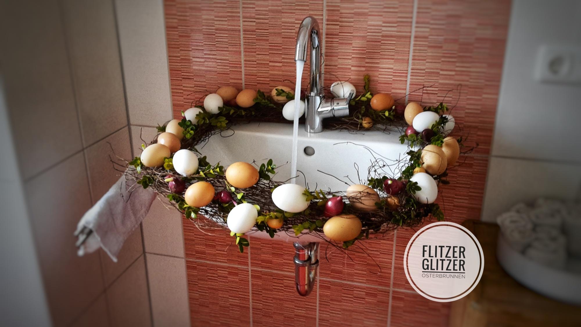 Gezeigt wird ein weißes Waschbecken mit laufendem Wasserhahn. Geschmückt ist es ringsum mit einem Kranz aus Naturmaterialien und ausgeblasenen Eiern in verschiedenen naturbelassenen Farbtönen.