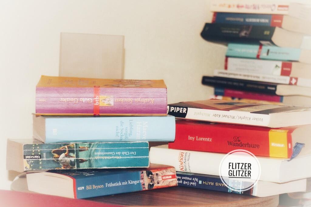 Nachttisch mit Bücherstapel. Im Hintergrund ist ein weiterer Bücherberg zu sehen.