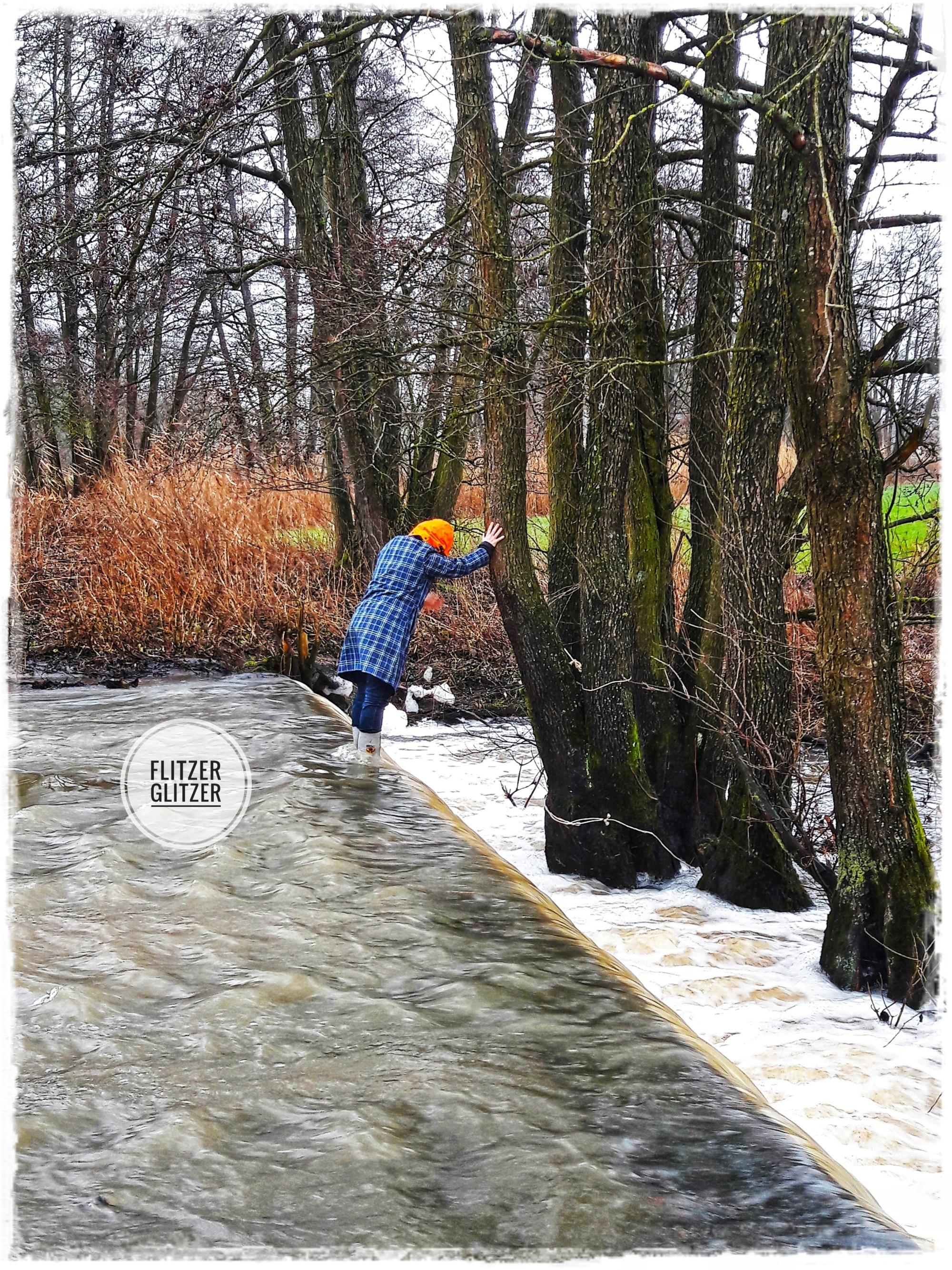 Glitzer steht in den Fluten eines Hochwasserüberlaufs der Altmühl. An einen Baum gelehnt beugt sie sich über den Wasserfall.