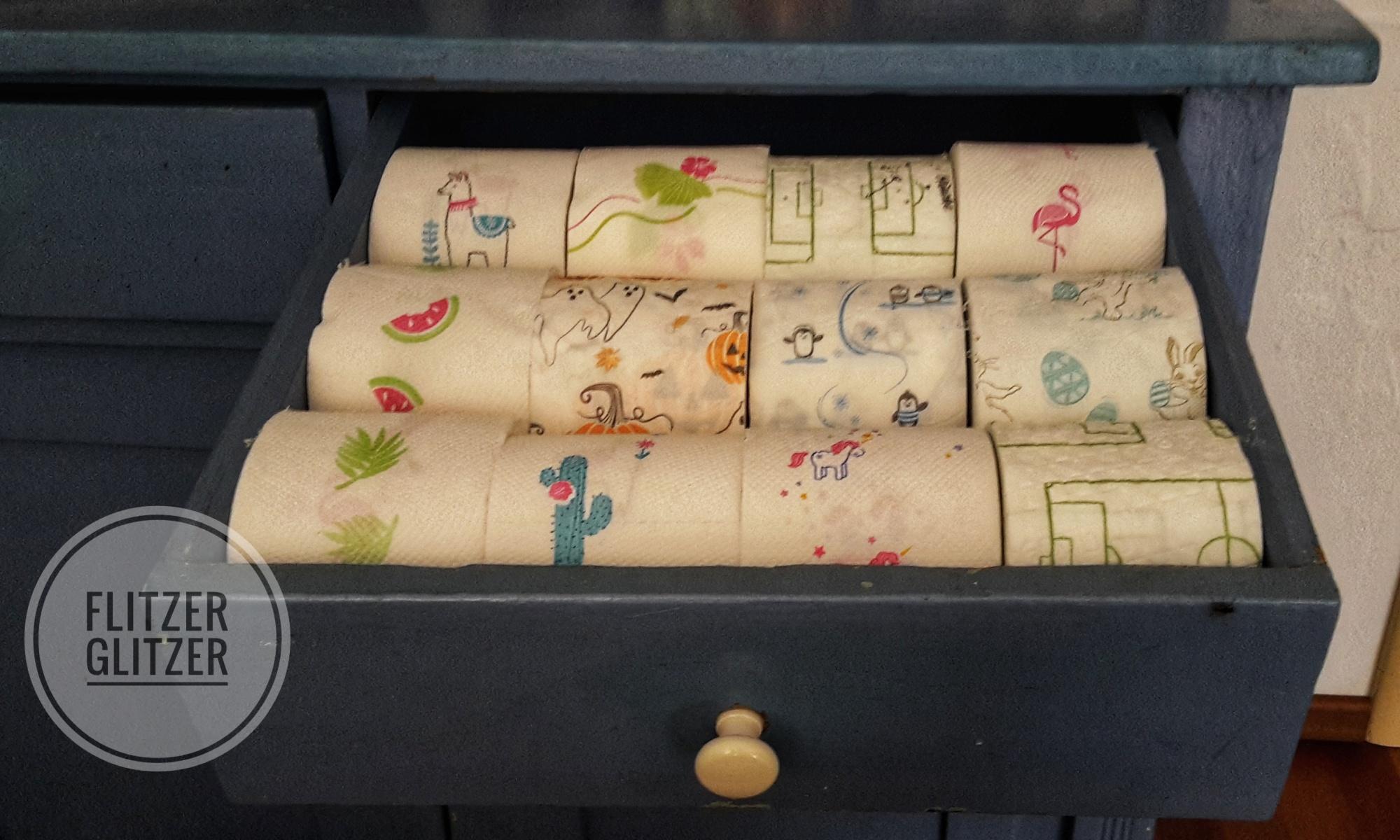 Bunte Toilettenpapiersammlung in einer blauen Schublade.
