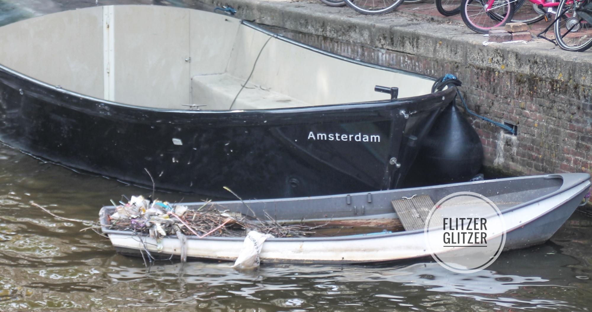 Das Bild zeigt ein kleines schwarzes Fischerboot, das auf den Namen Amsterdam getauft und original mit diesem Namen beschriftet ist. Davor ein noch kleineres abgewracktes Paddelboot in dem sich ein Vogel aus Ästen und allerlei Müll ein Nest gebaut hat.