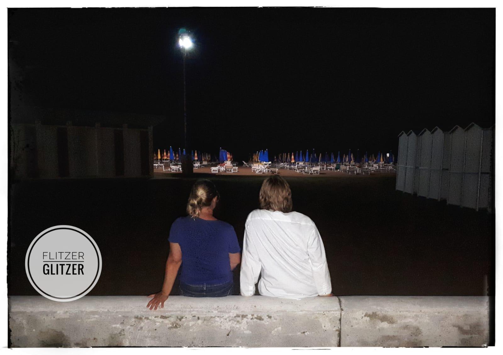 Flitzer und Glitzer sitzen auf einer Betonmauer und blicken auf das mondbeschienene Meer mit den für Italien typischen Liegenreihen und zusammengeklappten Sonnenschirmen