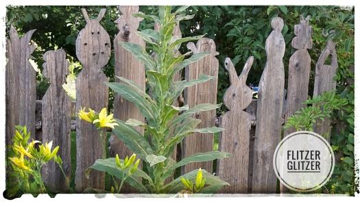 stehender Zaun aus ungehobelten Brettern, an deren oberen Enden Tierfiguren ausgesägt wurden
