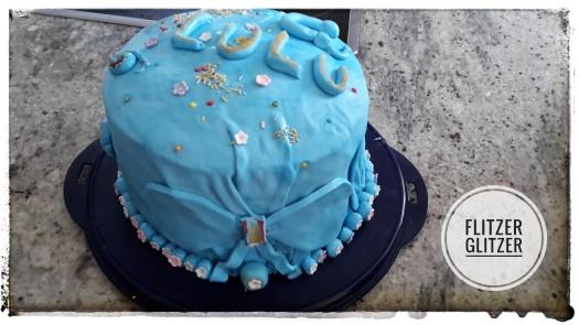 Eine über und über mit hellblauem Fondant überzogene und reichlich verzierte Torte.