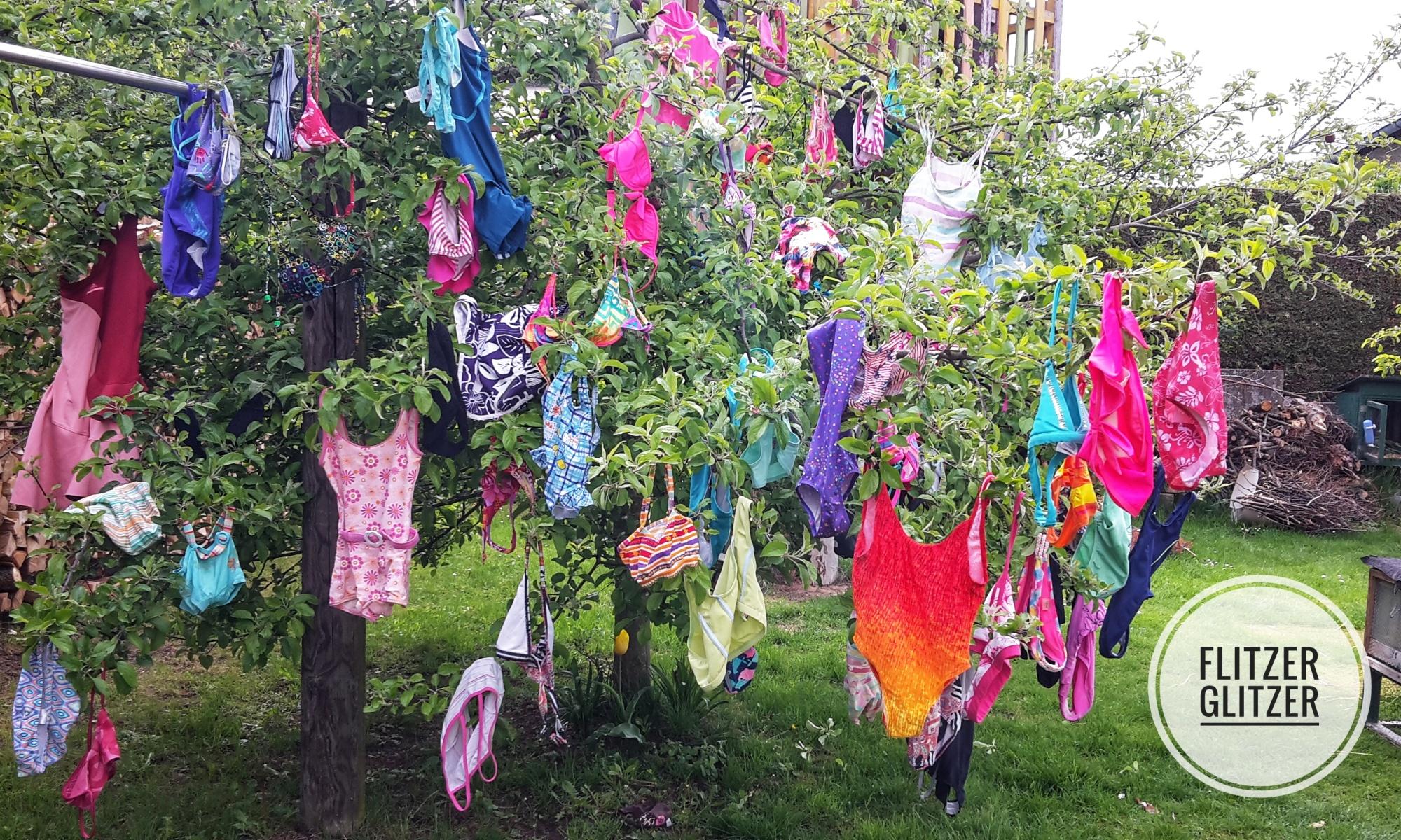 Wie Ostereier hängen die bunten Badeanzüge und Bikinis im Apfelbaum.