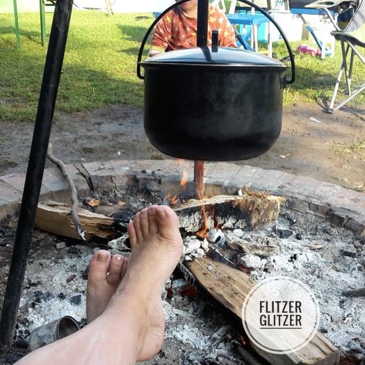 Lagerfeuer mit Kessel an Dreibein baumelnd.