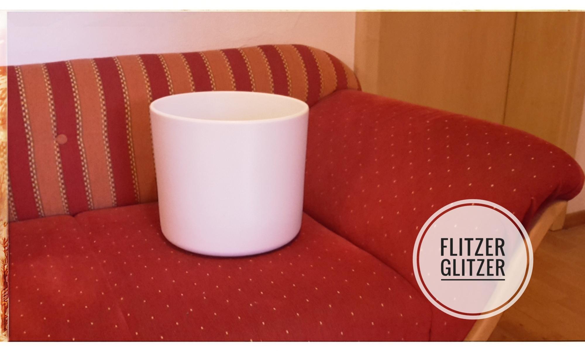 Einfacher weißer Übertopf auf rotem Sofa.