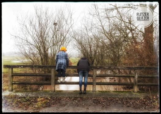 Flitzerglitzer hängen und stehen auf dem maroden Geländer einer in die Jahre gekommenen Brücke.