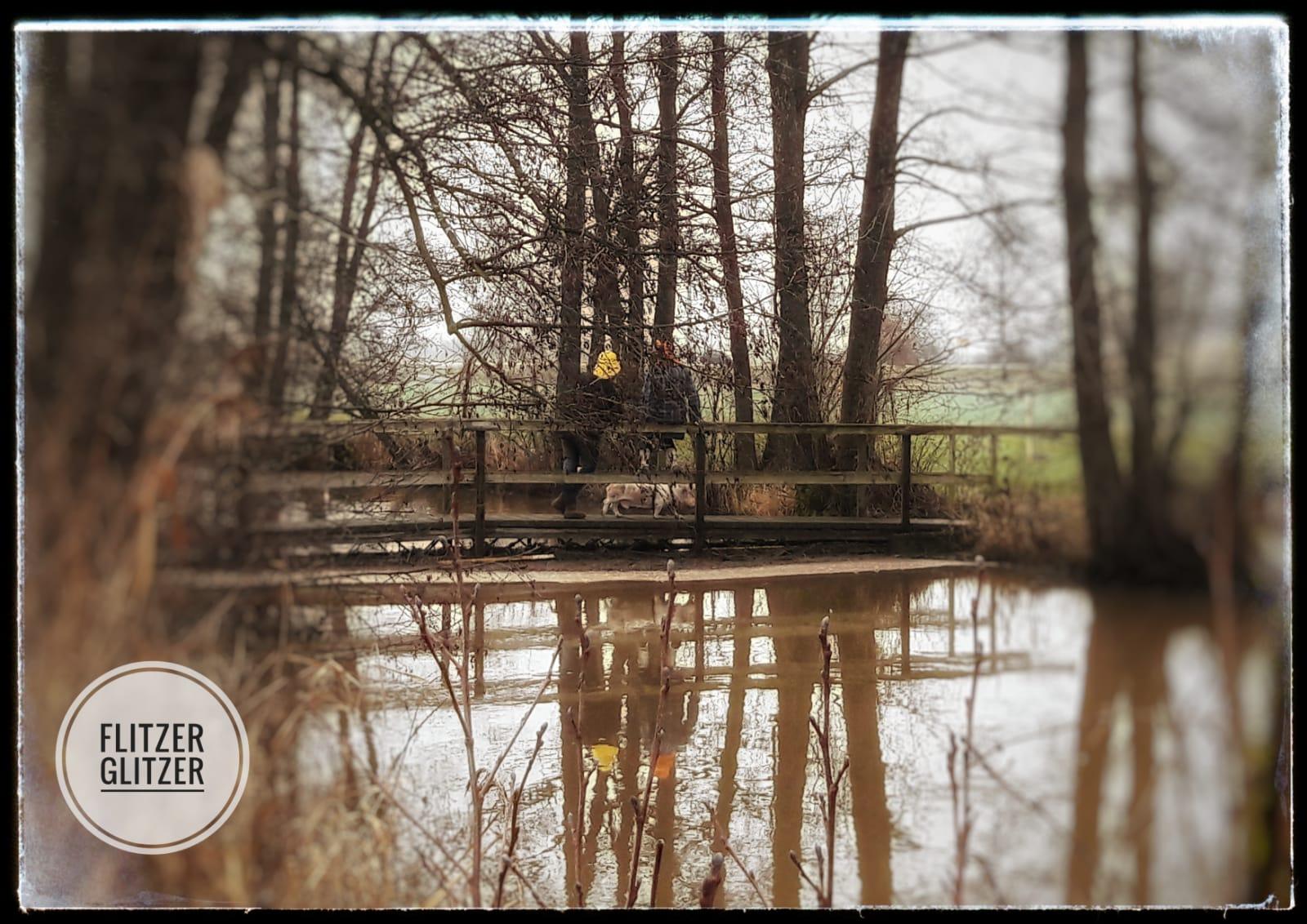 Das Hochwasser des kleinen Flusses reicht bis zur Unterkante dieser wunderschönen kleinen Holzbrücke.
