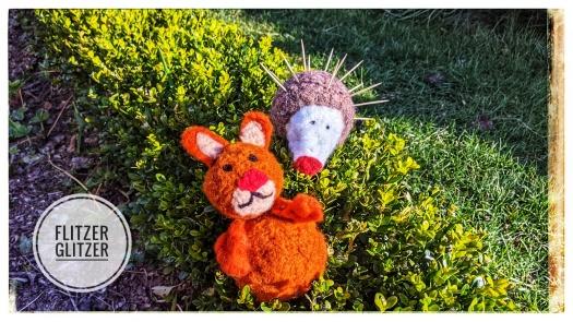 Hase und Igel haben es sich gemeinsam auf der kleinen Buxhecke gemütlich gemacht.